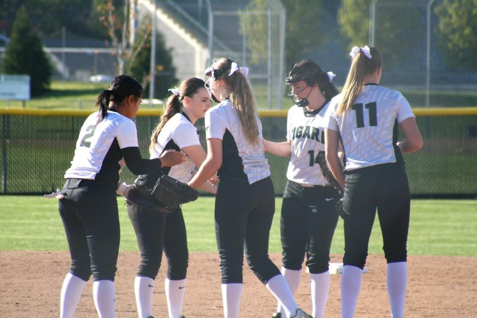 The+varsity+softball+infield+celebrates+after+getting+an+out+on+their+home+field.