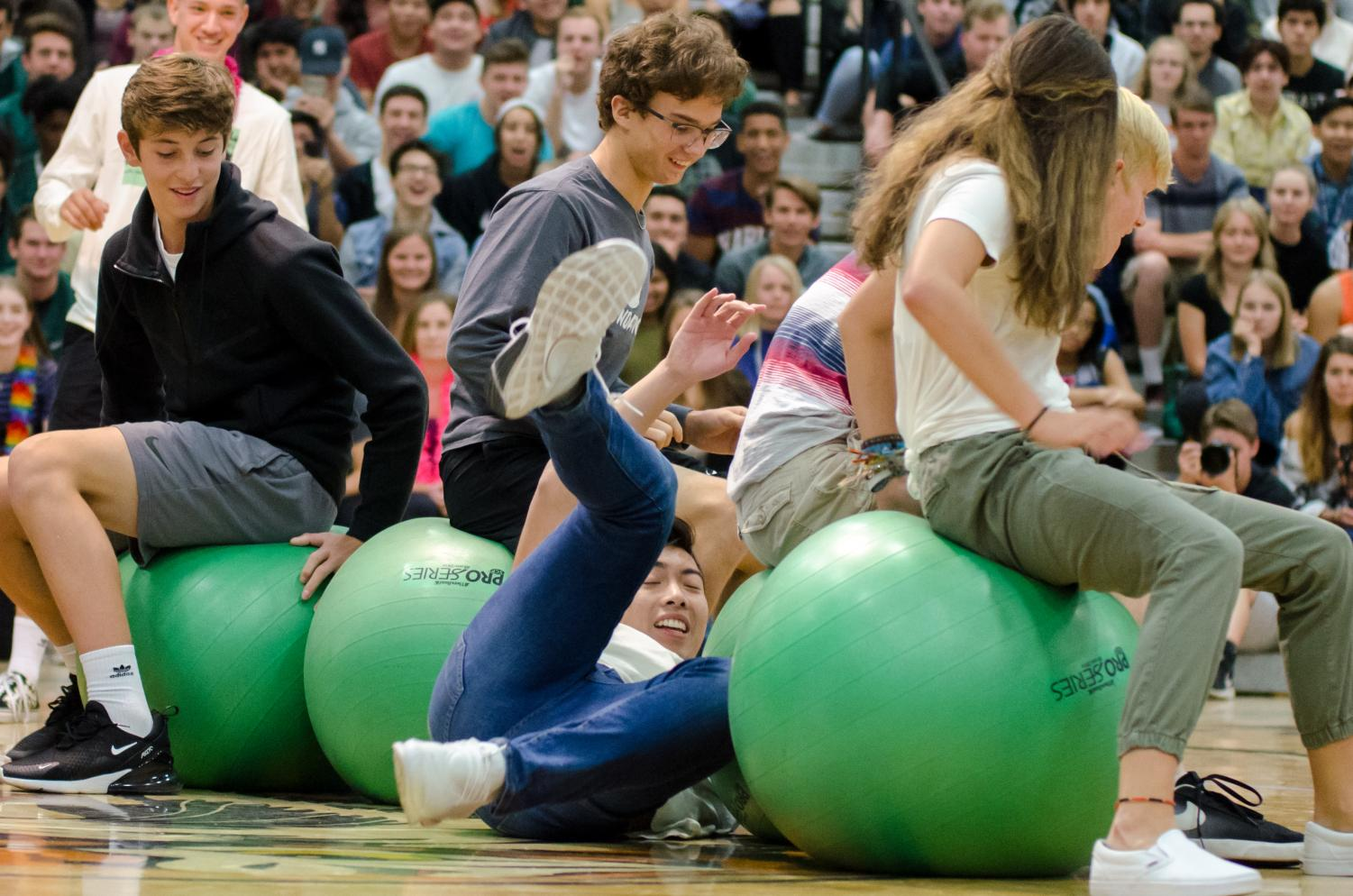 Students fight for the last seat in a 'musical chairs'-style game with exercise balls.