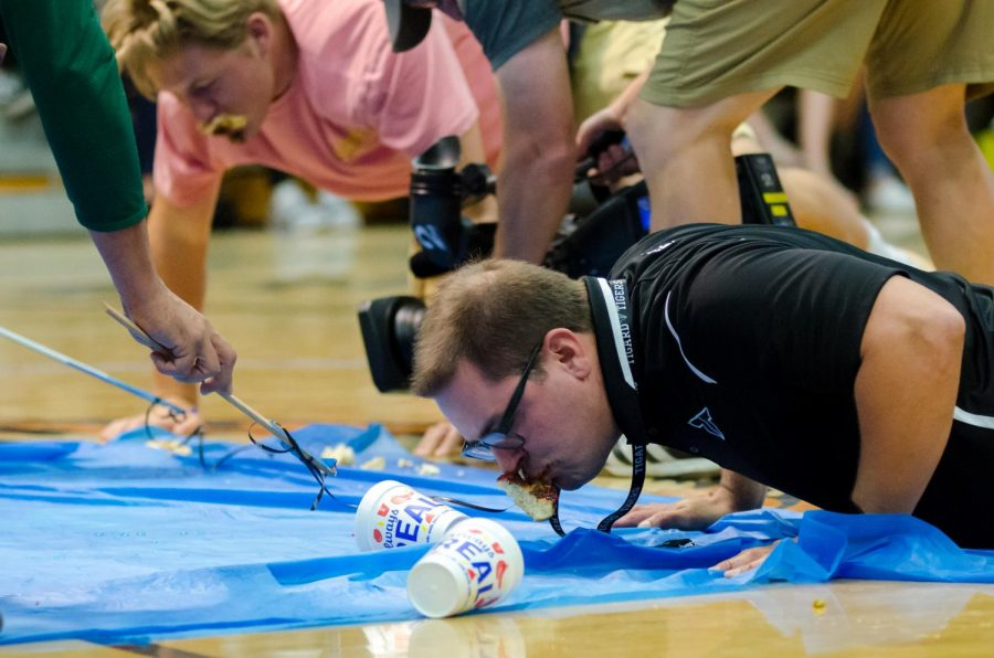 Vice Principal Andrew Kearl eats a donut off the floor in a speed-eating contest, taking care not to leave any crumbs.