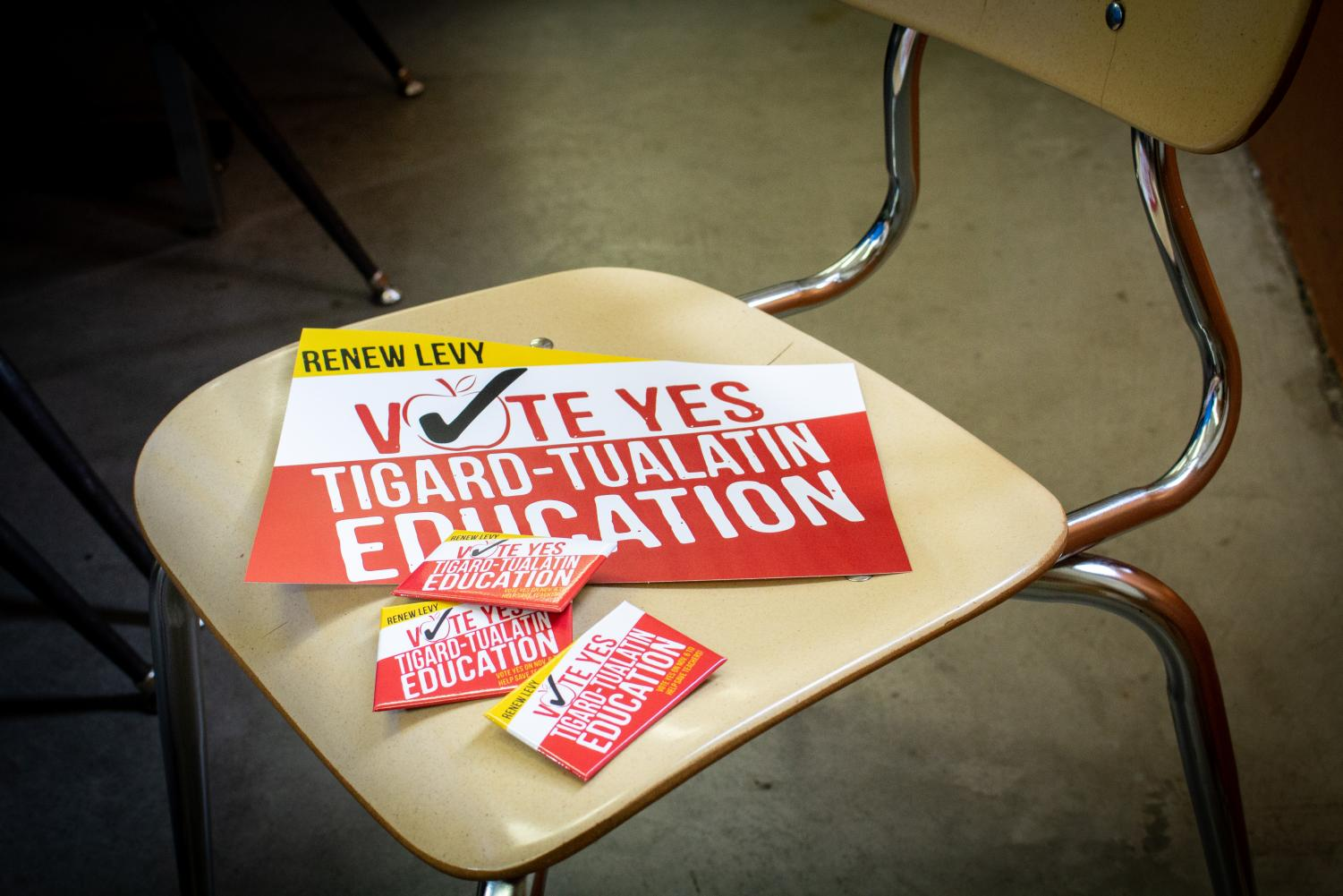 Buttons and flyers in support of the education levy sit on a classic classroom chair. The bond passed with 74 percent approval.