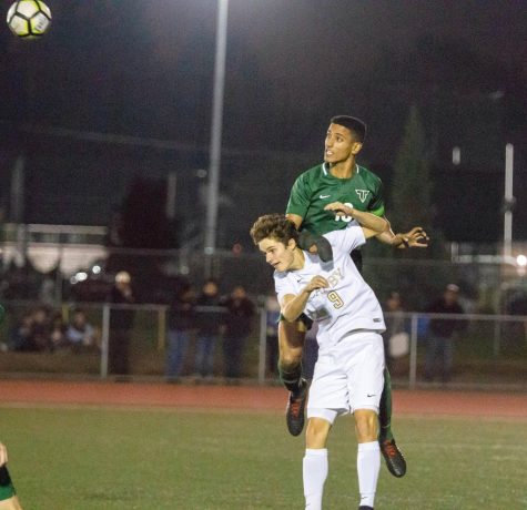 Senior defender Sajjad Al-Rikabi jumps over the Canby forward to win a header in the air during a 6-0 win on Oct. 18.  Al-Rikabi was named TRL Co-Player of the Year.