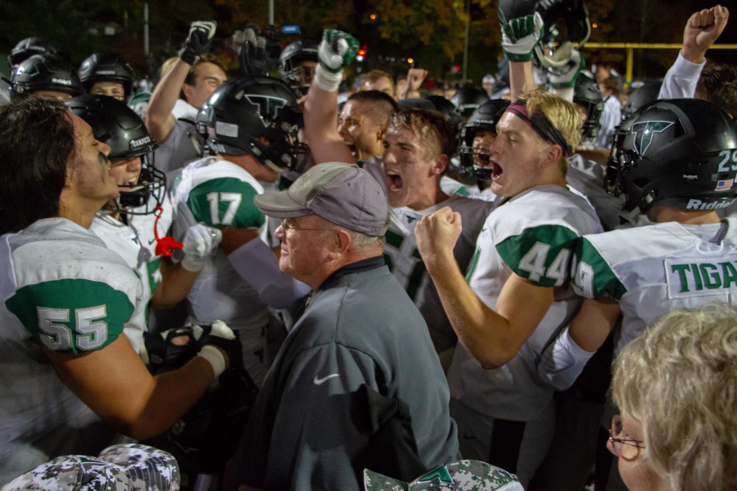 Players surround Coach Ruecker to celebrate their victory over West Linn. Ruecker, who has been a head coach for 42 years, 10 at Tigard, announced his retirement this week.