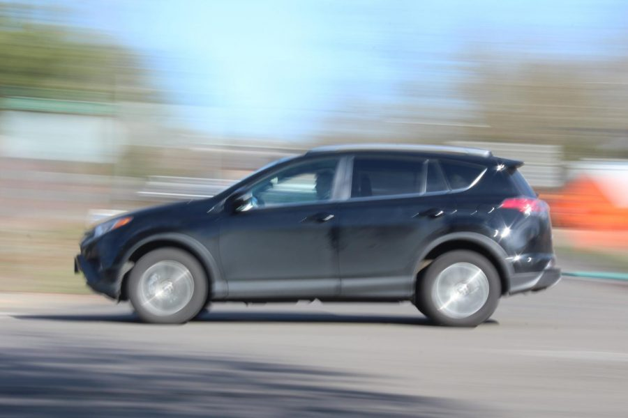 A car drives along Durham Road as Advanced Photography students capture panning shots. Red light cameras have been installed at three intersections along highway 99W in Tigard.