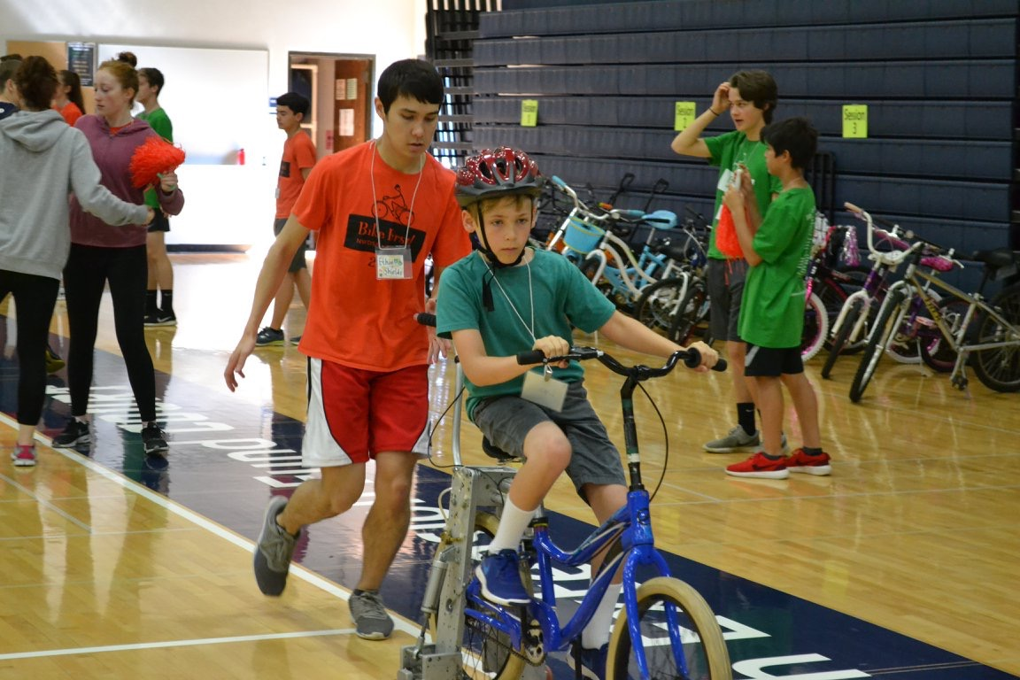 Ethan Shields helps a camper ride a bike. He has volunteered at Bike First! for nine years.
