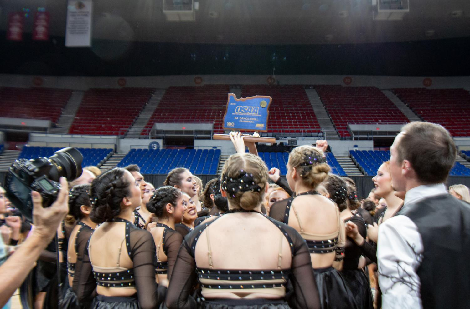 The Tigerettes hold up the state trophy on March 15. They won state for the second  year in a row.