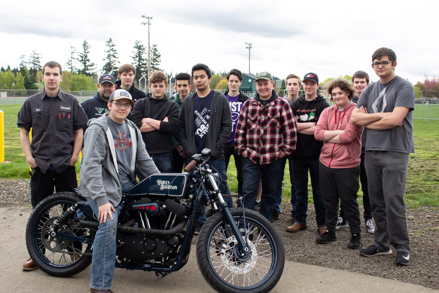 Junior Sterling McKinnon poses with Portland Flyer the bike he helped modify for a world-wide custom motorcycle competition. The Auto Electrical class gathered around to see the results.