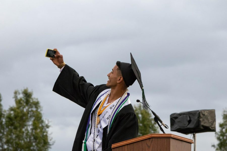 Sajjad Al-Rikabi poses for a selfie with his classmates during his commencement speech. He was one of 20 valedictorians and one of 11 who spoke during the graduation ceremony.