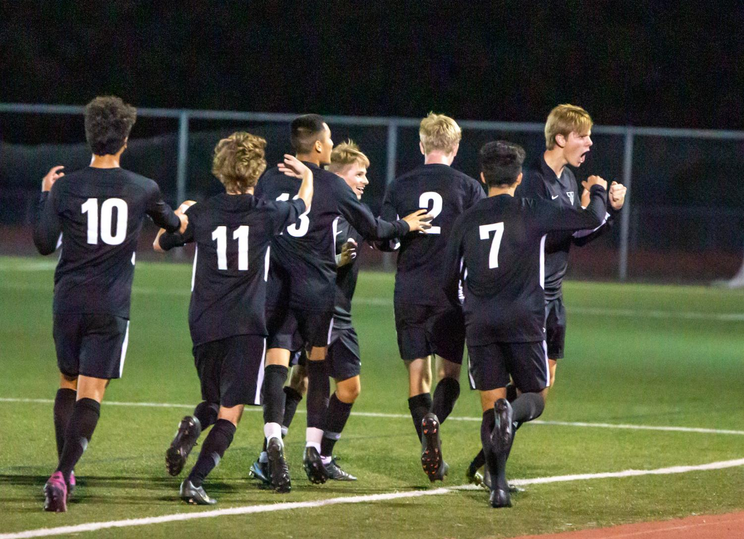 Teammates celebrate with Jared Debban after he scores the game's only goal in the boys varsity soccer defeat of Tualatin on Sept. 12.