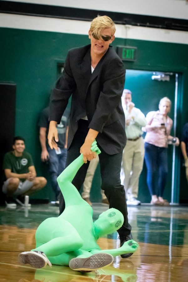 Andrew Carter drags an alien across the gym floor at the Welcome Back Assembly. The assembly had an Area 51 theme.