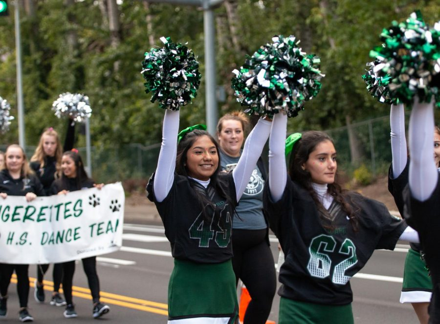 Varsity+Cheer+helps+lead+the+homecoming+parade+by+cheering+loudly+and+keeping+the+crowd+of+people+entertained+as+they+anticipated+the+rest+of+the+parade.