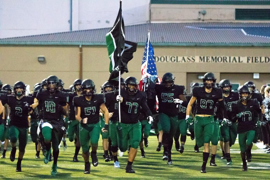 The+Varsity+football+team+runs+onto+the+field+on+Oct.+4th+to+start+up+the+homecoming+game.+%E2%80%9CIt+was+weird+because+knowing+that%E2%80%99s+the+last+hoco+game+I%E2%80%99ll+ever+play%2C%E2%80%9D+said+Senior+Johnny+Nomani.+%E2%80%9CI+played+as+hard+as+I+could+but+was+cold+for+the+most+part+because+we+killed+them.%E2%80%9D+The+team+ended+up+winning+56-0+against+Sprague%2C+making+it+a+homecoming+game+they+will+never+forget.