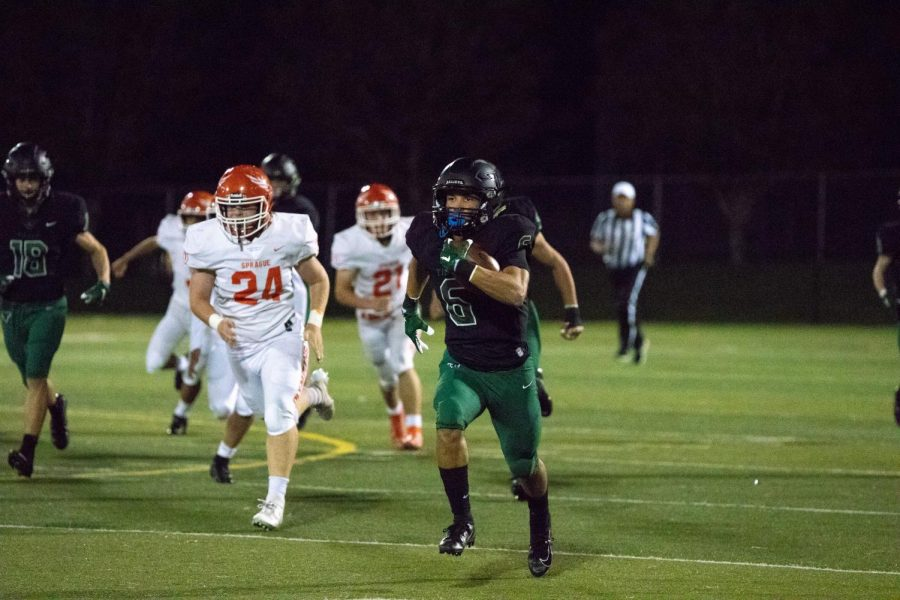 "Senior Max Lenzy pushes through the lines of defense to score another goal for Tigard. ""It feels great just having everyone coming out to the game and everyone just supporting my team and I,"" Lenzy said. The Tigers managed to have a shutout game against Sprague with a score of 56-0."