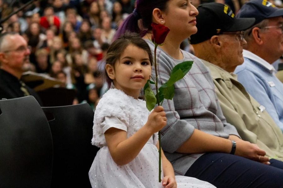 A young girl holds her mother's rose. At the assembly roses are presented to each veteran to honor them for their years of service.