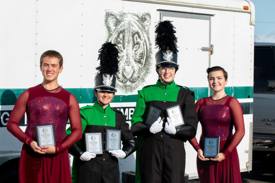 Senior Ian Harrington, sophomore DJ Johnston and seniors Natalie Scharn and Marta Berger hold up the plaques the team received at the NWAPA Championship on Nov. 2.