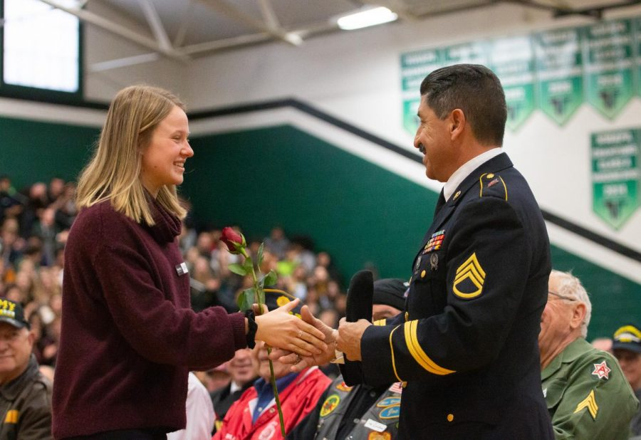 Senior Sarah Gentry presents Head Custodian Gus Jaramillo a rose for his years of service in the Army.