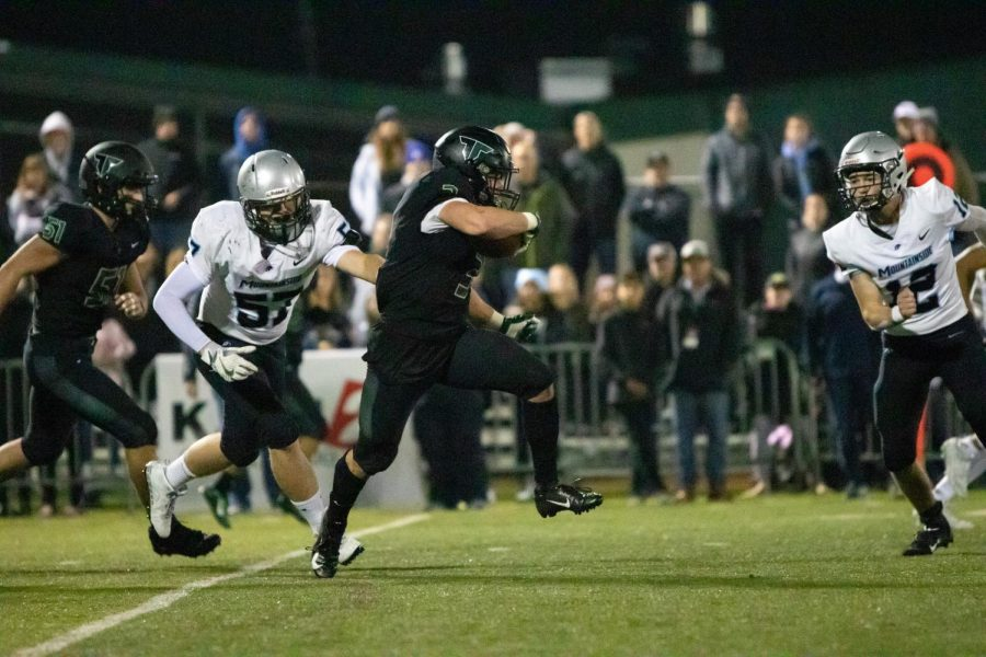 Senior Hunter Gilbert rushes through Mountainside's defense to score a touchdown. The Nov. 15 playoff game was Tigard's first and last loss of the season with a score of 31-34 in overtime.