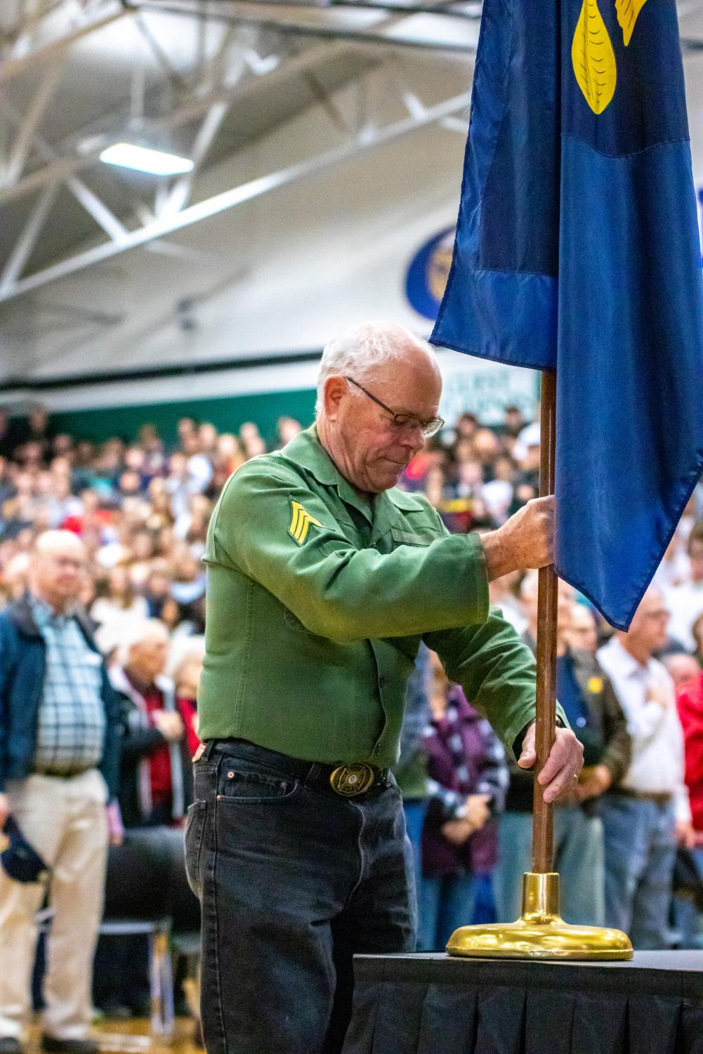 Mark Lueck helps Head Custodian Gus Jaramillo with the presentation of the colors and placing the Oregon state flag.