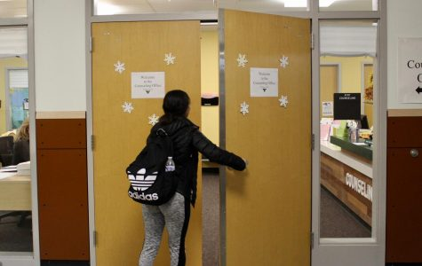 A student is pictured entering the counseling office. The doors must open outward due to safety regulations.