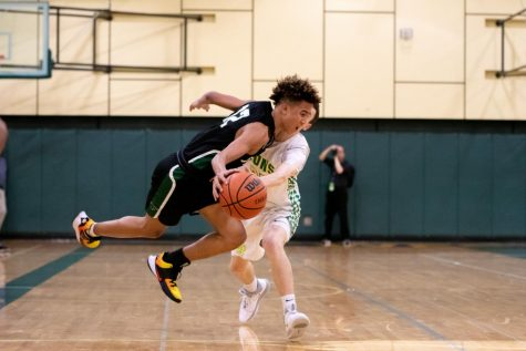 "Freshman Malik Brown maneuvers around West Linn opponent on Feb 17. ""Everyone on the team was very accepting of me being a freshman and it makes me feel really good they have my back,"" Brown said."