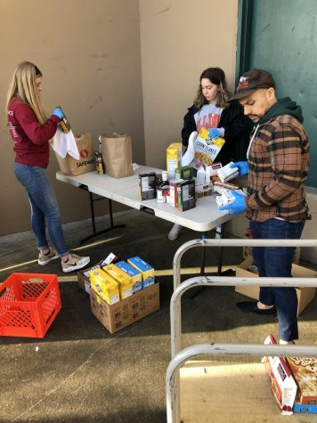 Student and community volunteers work to sanitize food before sorting it. So far, Packed with Pride has collected commitments from over 500 volunteers.