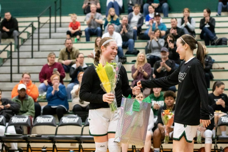 "Senior Emily Paulson receives her gift from freshman Hailey Shimojima during senior night against Oregon City. ""I am going to miss playing with my teammates and getting to be around them all the time,"" Paulson said."