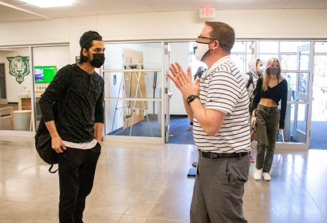 """Principal Brian Bailey greets senior Abdallah Ghallan. """"On the first day we had students in the building, I literally got goosebumps,"""" Bailey said. """"I knew it was going to look and feel different, but it was also our first real step back toward normalcy."""""""